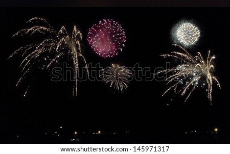 Multiple colorful simultaneous fireworks chargers exploding in pitch black sky
