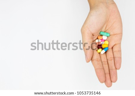 multiple colors pills in  hand  on white background, Taking Your Medication.
