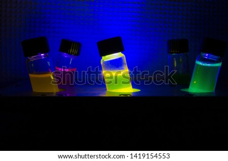 Multiple colourful light induced catalyst photochemical reaction side view in glass vial under UV light in a dark chemistry laboratory for biomedical research #1419154553