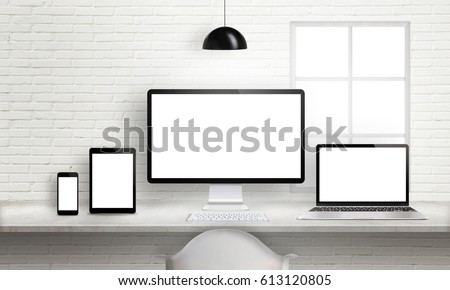 Multiple devices on office desk for responsive web site design presentation. Brick white wall in background. #613120805
