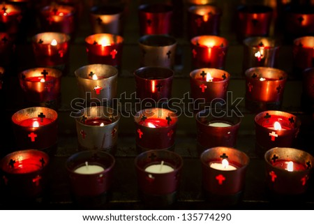 Multiple devotional candles lighting a darkened Roman Catholic Basilica. Image shows candle holders most all with lit candles. The lit candles provided the only light for this shot.