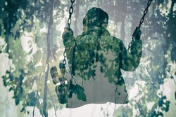 Multiple exposure of kid on swing and gorgeous green leaves