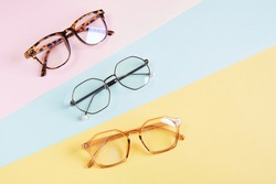 multiple eyeglasses on a multicolored background of pastel colors, geometric background, pink yellow and light blue colors, trendy eyeglass frames copy space