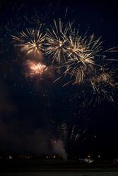 Multiple golden fireworks exploding in the sky