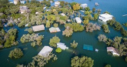 multiple houses half under water Aerial drone views high above Flooding caused by Climate Change