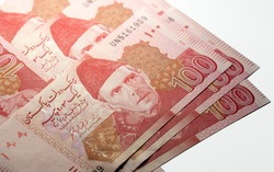 Multiple Hundred (100) Rupees Pakistani currency bank notes on a white background - PKR