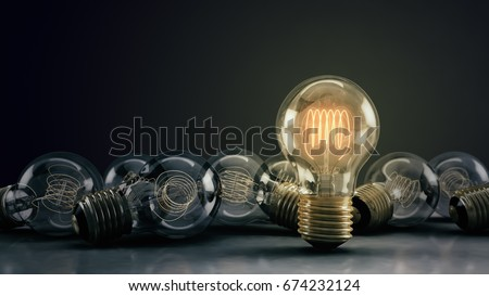 Multiple incandescent light bulbs on a reflective surface & dark background.  One bulb illuminated, standing out from the rest.  Great for conveying a big idea/unique business thoughts.  3D render.