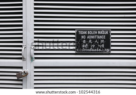 Multiple language No Admittance signboard in English, Bahasa Indonesia, Chinese and Hindi, mounted on a metal louver door secured with a padlock.