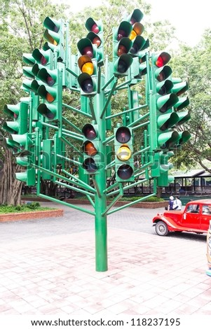 Multiple large traffic lights post made from green metal, taken on a cloudy day