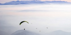 Multiple para-gliders descending on a foggy valley at dusk.