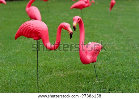 Multiple pink plastic flamingos on a lawn.