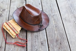 Multiple pipes pan flute and leather cowboy hat lying on square-edged flooring, copy space
