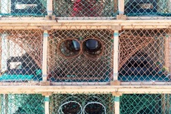 Multiple rope netting lobster pots or traps stacked high along a wharf. Containers are made from an orange wire, nylon netting, and in a square shape. There's no bait in the pots, all are empty.
