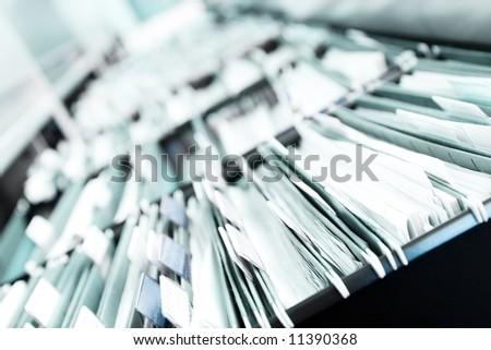 "Multiple rows of filing cabinets in an office or medical establishment, overflowing with files.  Narrow depth of field to emphasize the ""neverending"" feeling"