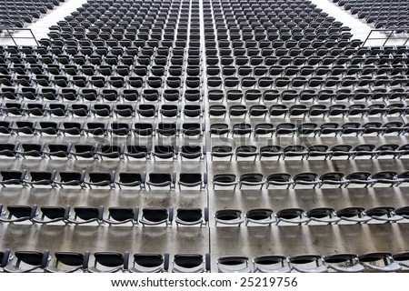 Multiple rows of grey seating with narrow depth of field into infinity