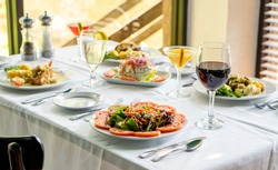 Multiple seafood, steak and salad entrees with wine, martini glass and silverware for fine dining, on a white tablecloth.