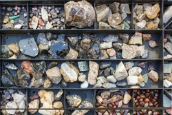 Multiple semi precious gemstones on wooden board close up