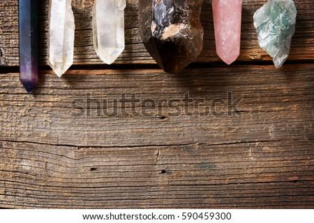 Multiple semi precious gemstones on wooden boardfluorite, quartz, smoky quartz, rose quartz.  #590459300