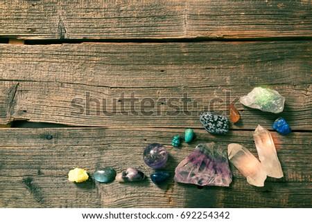 Multiple semi precious gemstones on wooden boardfluorite, quartz, smoky quartz, rose quartz.  #692254342