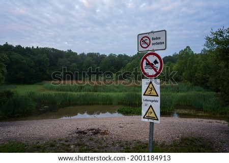 Multiple signs in a forest infront of a dirty pond indicating it's not allowed to swim there and that it is very dangerous even for the dog Foto stock ©