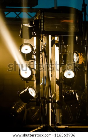 multiple spotlights on a stage lighting rig