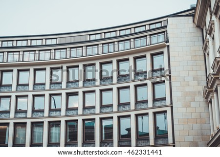 multiple storied office building with stone facade and curved