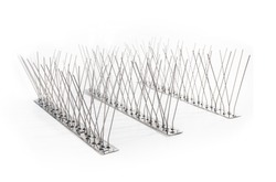 Multiple strips of bird spikes in a row. Stainless bird spikes prevent pigeons, sparrows, seagulls, swallows from landing, roosting or nesting.  Concept for humane pest control. Isolated on white.
