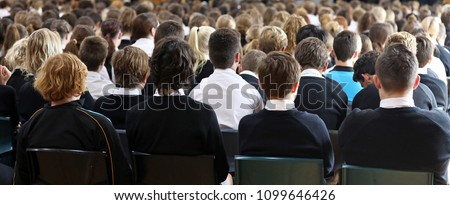 multiple students seated at assembly at high school facing the front listening attentively. school days life. backs of heads, facing the front, group shot of school age kids. Modern schooling. chairs