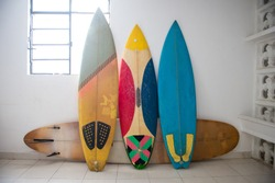Multiple surfboards staying by the wall inside of the house with the white walls. Tropical lifestyle. Downshifting concept.
