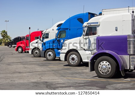 Multiple trucks park in a large parking lot. #127850414