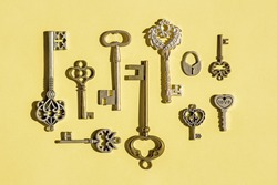 Multiple vintage keys isolated on a yellow background. Image of old antique keys,  top view, flat lay