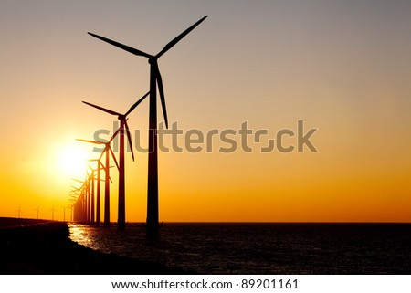 Multiple Windturbines producing alternative energy during a sunset