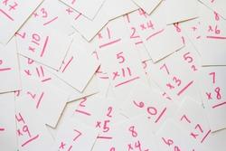 Multiplication flash cards spilled onto a pile; scattered math flash cards background
