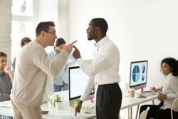 Multiracial african and caucasian colleagues disputing having disagreement at work blaming each other in mistake, diverse coworkers arguing about project, having conflict fight at workplace concept