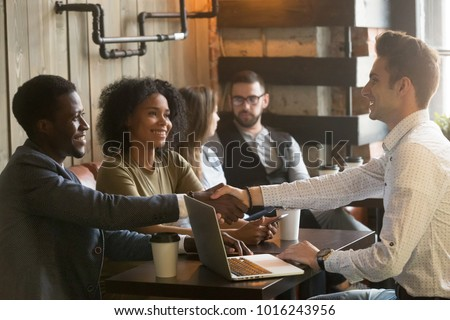 Multiracial african and caucasian men handshaking at meeting in cafe, diverse friends greeting sitting at coffeeshop table or black couple making deal shaking hands to white businessman with laptop