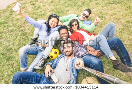 Multiracial best friends taking selfie at meadow picnic - Happy friendship fun concept with young people millennials having fun together outdoors on spring summer time - Neutral afternoon filter