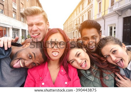 Multiracial best friends taking selfie outdoors in urban contest - Happy young people having fun together - Multi ethnic and Friendship concept - Soft vintage warm filtered look