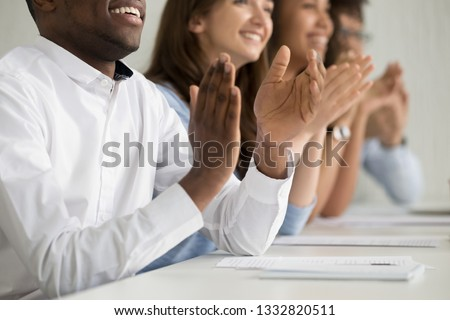 Multiracial business audience people group smiling applauding sitting at conference table clapping hands at corporate training seminar meeting, appreciation applause ovation concept, close up view