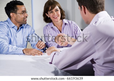 Multiracial business meeting in boardroom, shaking hands.  Shallow DOF, focus on handshake