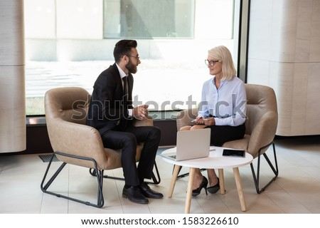 Multiracial business partners talk sharing ideas considering thoughts working on laptop at company meeting, diverse businesspeople brainstorm talking at interview or briefing, cooperation concept