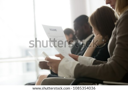 Multiracial business people waiting in queue preparing for job interview concept, diverse unemployed vacancy applicants holding reading cvs getting ready, human resources concept, focus on resume