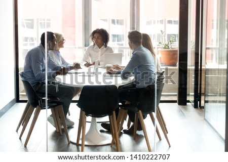 Multiracial business team people with african female leader talk sit at modern office boardroom table, diverse employees discuss work plan together at corporate staff group meeting behind glass door