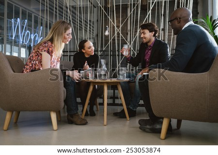 Multiracial business team sitting in office lobby discussing new business ideas. Young man drinking water. Happy young people during meeting.