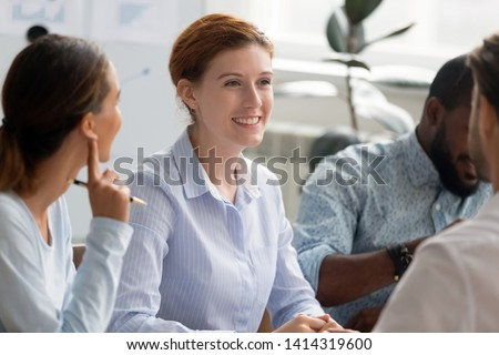 Multiracial businesspeople sitting at office desk with focus on young smiling female employee listening male colleague. Business team having fun conversation, joking talking, discussing project