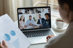 Multiracial businesspeople talk speak on video call discuss financial paperwork statistics online, diverse colleagues have distant webcam conference on laptop, engaged in briefing on web together