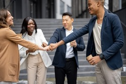 Multiracial businessteam bumping fists each other on city street. Concept of modern successful business people. Idea of business cooperation. Remote and freelance work. Joyful people wear formal wear