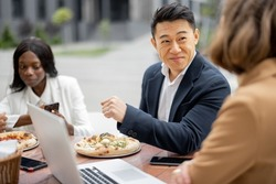 Multiracial businessteam having lunch with pizza and talking at outdoor cafe. Concept of teambuilding and corporate event. Idea of rest and leisure on job. People at table with digital devices