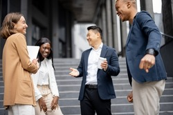 Multiracial businessteam standing and talking on city street. Concept of modern successful business people. Idea of business cooperation. Remote and freelance work. Smiling people wearing formal wear