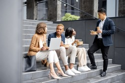 Multiracial businessteam talking, eating and drinking coffee while sitting on stairs in city. Concept of rest and break on job. Idea of business cooperation. Caucasian businesswoman with laptop