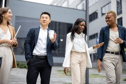 Multiracial businessteam walking and talking on city street. Concept of modern successful business people. Idea of business cooperation. Remote and freelance work. Joyful people wearing formal wear